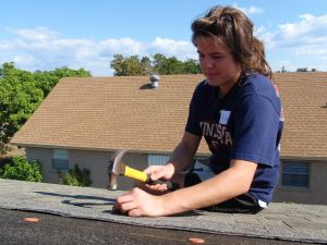 Kelsey Plumedahl, 19, a University of Minnesota student, helps shingle a roof at a Habitat for Humanity home in Hobe Sound.